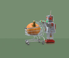 Toy robot pushing miniature shopping trolley with pumpkin