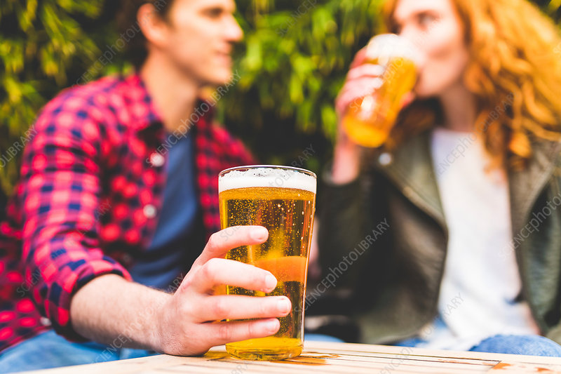 Couple drinking beer in pub garden