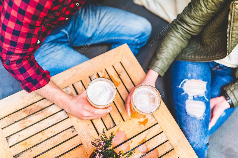 Couple holding pints of beer, in pub garden, overhead view