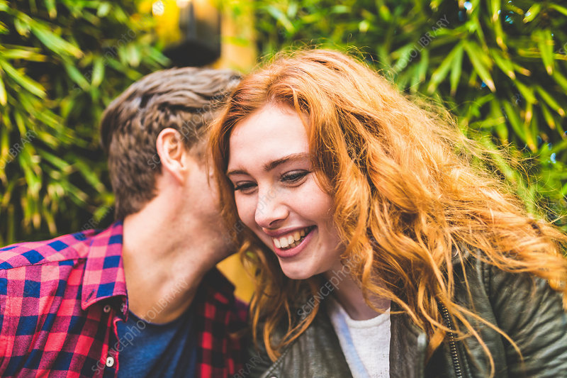 Couple outdoors, man whispering in woman's ear