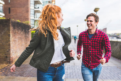 Couple outdoors, running along street, laughing