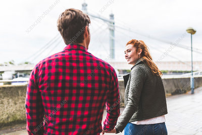 Couple walking outdoors, hand in hand, rear view