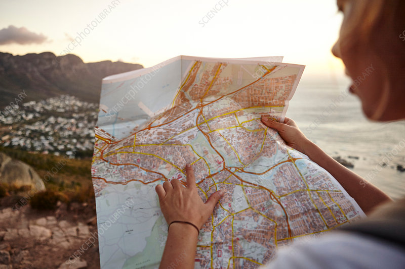 Young woman hiking, looking at map, Cape Town, South Africa