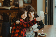 Two female friends, sitting in cafe, taking selfie