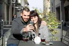 Young couple sitting outside cafe, taking selfie