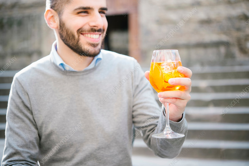 Portrait of young man, outdoors, raising glass