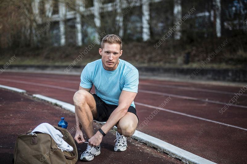 Young man crouching beside sports track, tying shoelaces