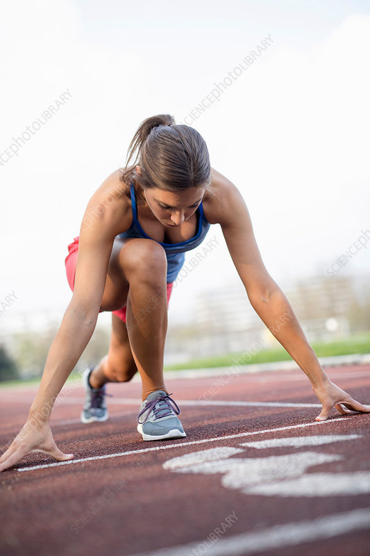 Young woman on sports track, stretching