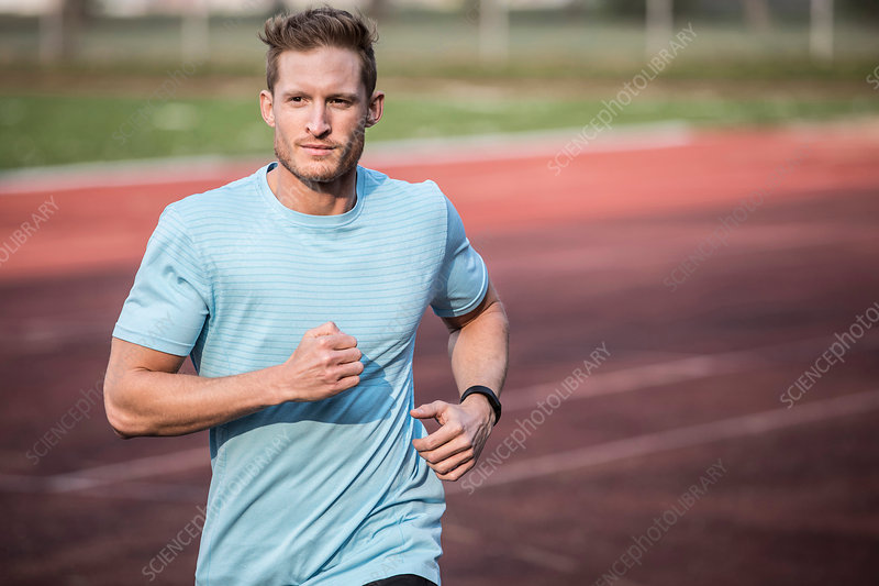 Young man running on sports track