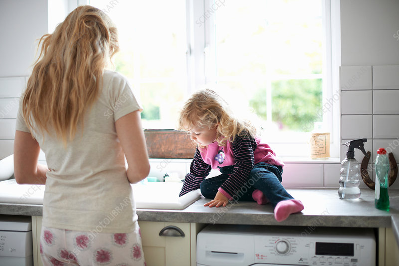 Mother and daughter in kitchen, daughter helping mum