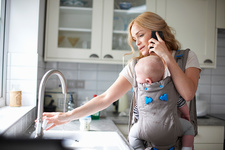 Woman holding baby boy in sling, doing washing up
