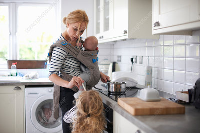 Woman cooking in kitchen with kids