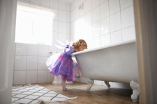 Young girl dressed in fairy costume, looking in bath tub