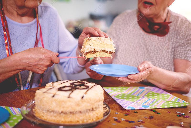 Senior women serving birthday cake at party