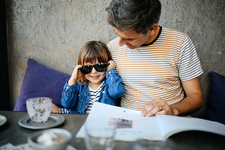 Girl playing with father's sunglasses in cafe