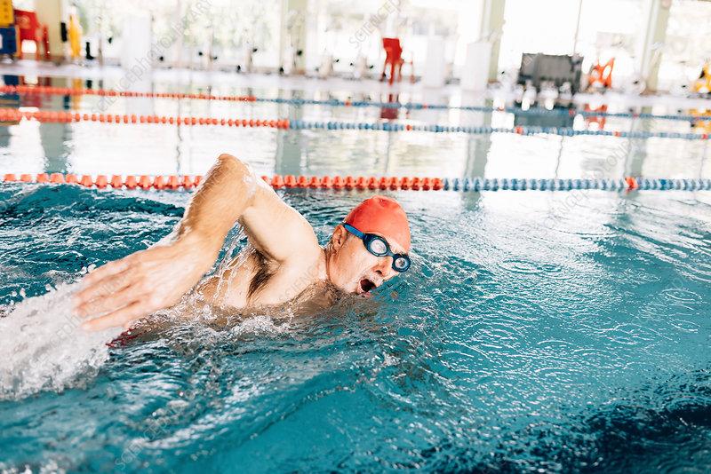 Senior man swimming in swimming pool