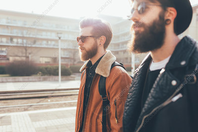 Side view of two male hipster friends wearing sunglasses