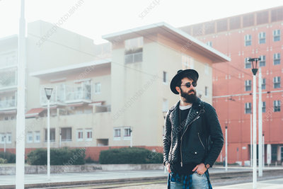 Young male hipster waiting at city tram station