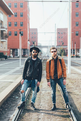 Two male hipster friends standing on city tram lines