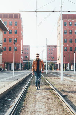Cool young bearded man walking along city tram lines