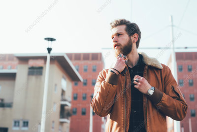 Young male hipster stroking beard on housing estate