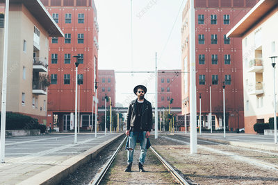Portrait of young male hipster standing on city tram lines