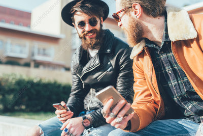 Two young male hipsters sitting on wall with smartphones