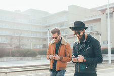 Two male hipsters looking at smartphones