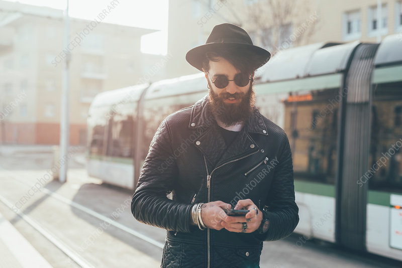 Young male hipster looking at smartphones