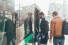 Two young men boarding tram at city tram station
