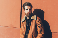 Portrait of cool bearded man leaning against orange wall