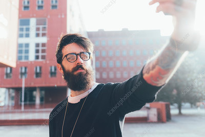 Cool young male hipster taking smartphone selfie in city