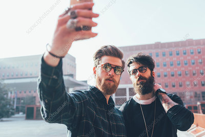 Two cool male hipsters taking smartphone selfie in city