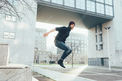 Young male hipster jumping mid air