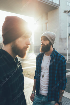 Portrait of two male hipsters in knit hats in city sunlight