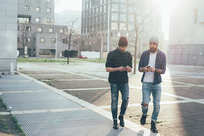 Two male hipsters walking, looking at smartphones