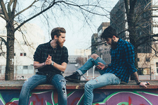 Two male hipsters sitting on wall looking at smartphone