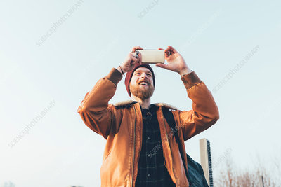 Happy male hipster taking selfie against blue sky