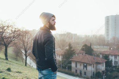 Young male hipster looking out over cityscape