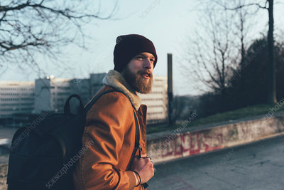 Young male hipster walking in park
