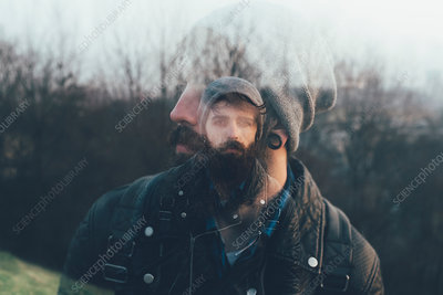 Double exposure portrait of bearded young male hipster