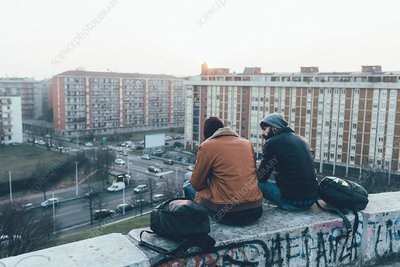 Rear view of two male hipsters sitting on wall