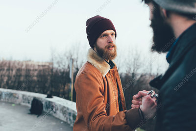 Two young male hipsters fist bumping in park