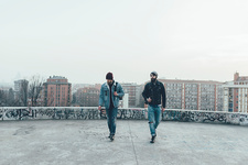 Two young male hipsters walk on city roof terrace