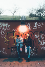 Portrait of two male hipsters leaning against graffiti wall