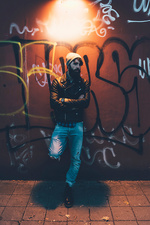 Portrait of cool male hipster leaning against graffiti wall