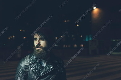 Young male hipster on city street at night looking away