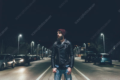 Young male hipster on city street looking away at night