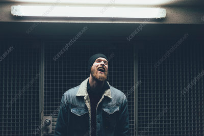 Young male hipster laughing in dark city doorway at night