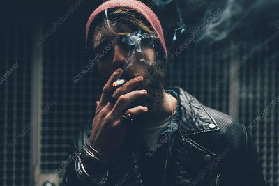 Young male hipster smoking cigarette in dark city doorway